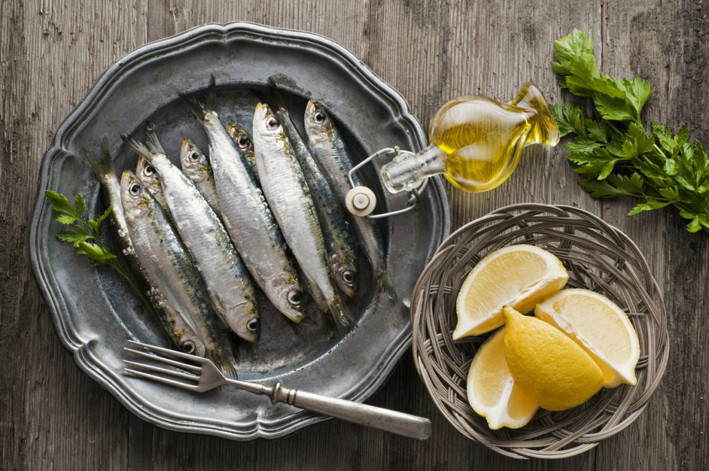 Fresh raw sardines with parsley and lemon on wooden background